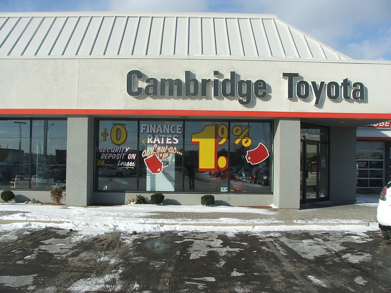 Graphic lettering in white, yellow and red at car dealership